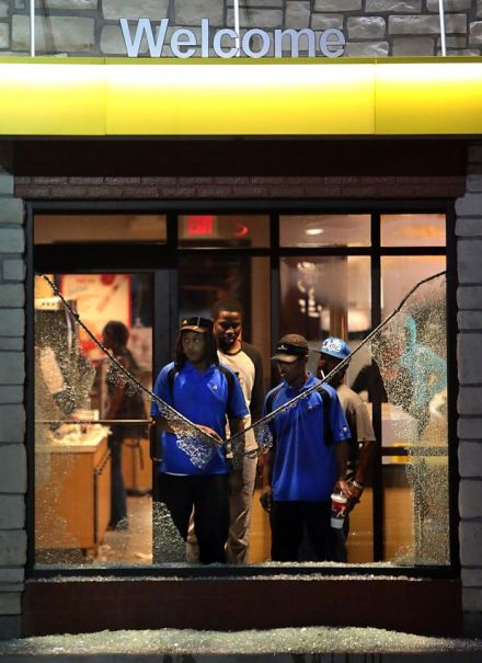 Two workers at the McDonald's store on W. Florissant in Ferguson watch as military-armed riot police attempt to suppress a mass demonstration on the night of August 17, 2014. (From the St. Louis Post-Dispatch)