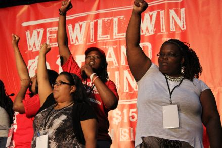 Workers raise their fists at the first ever nationwide fast food workers convention, held in Villa Park, Illinois at the end of July. (From Vice)